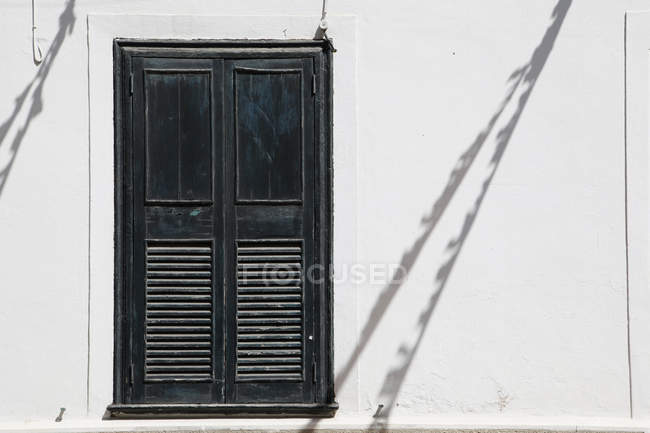 Closed window shutters on white building wall — Stock Photo
