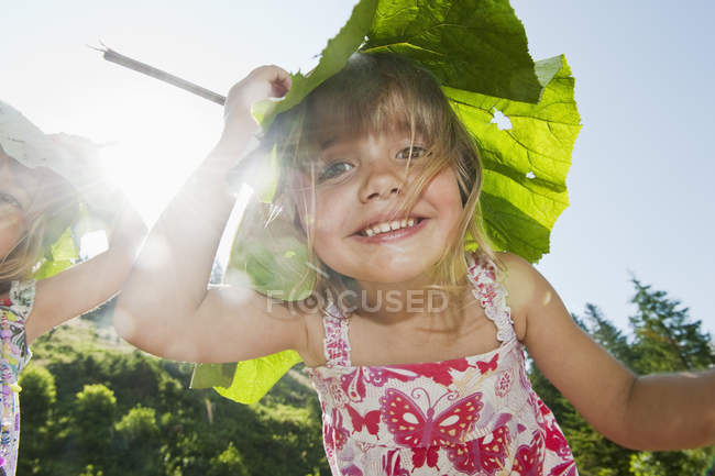Girls carrying leaves on head and looking in camera — Stock Photo