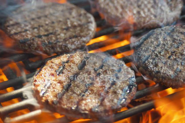 Burger Bratlinge auf Grill Rost mit Feuer Flammen — Stockfoto