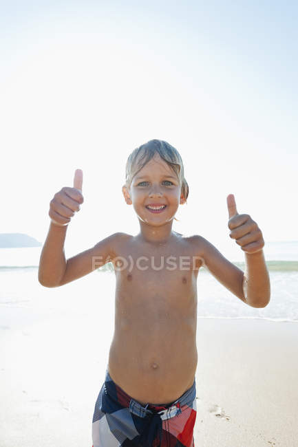 Portugal, Boy showing thumbs up, standing on beach — Stock Photo