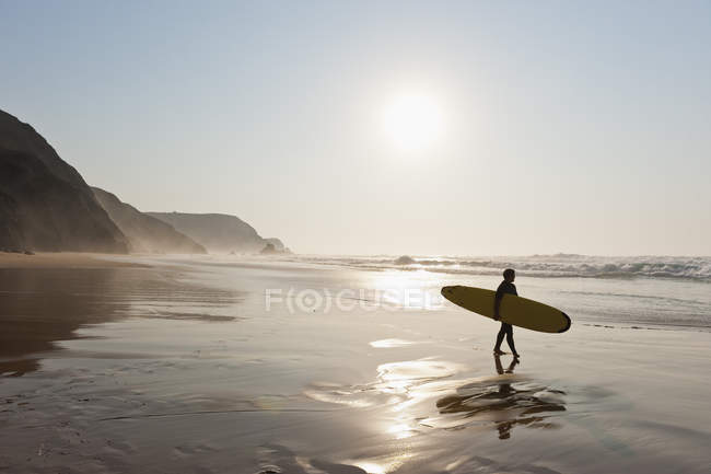 Surfer walking on beach — Stock Photo