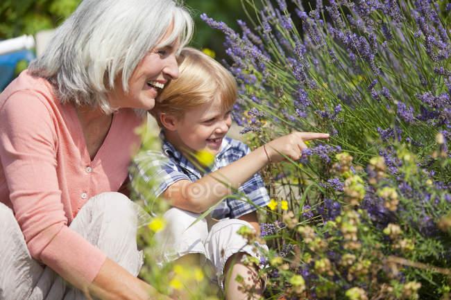 Mulher madura com menino no jardim — Fotografia de Stock