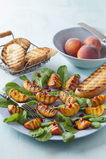Peach salad garnished with pomegranate seeds — Stock Photo