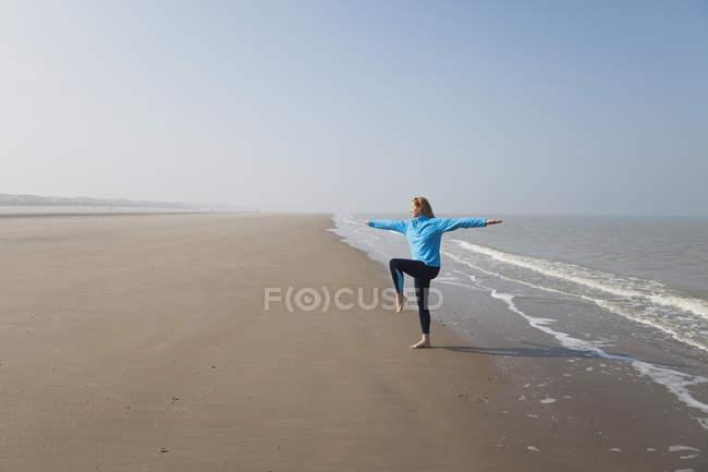 Bélgica, Mujer madura de pie en la pose del árbol en el Mar del Norte - foto de stock