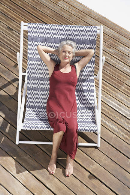 Senior mujer relajante en silla de cubierta - foto de stock