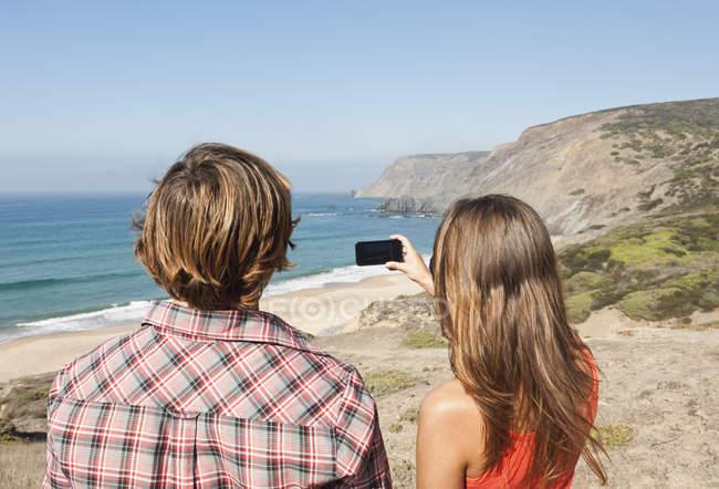 Беручи фотографії пара на пляжі — стокове фото