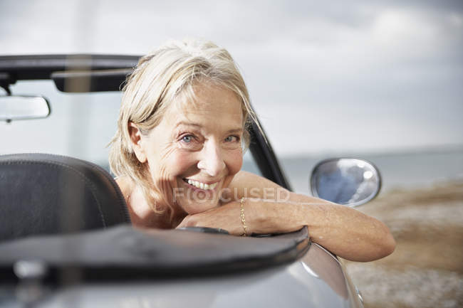 Senior woman driving in convertible car — Stock Photo