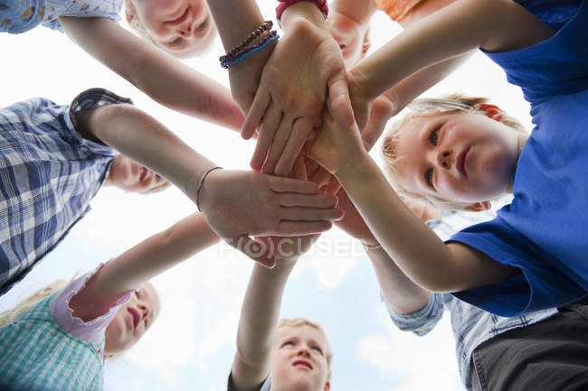 Group of children putting hands together — Stock Photo