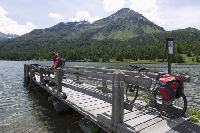 Svizzera, uomo maturo in piedi sul molo con il lago di Sils — Foto stock