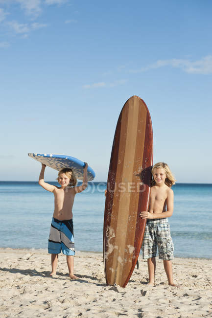 Children standing with surfboards — Stock Photo