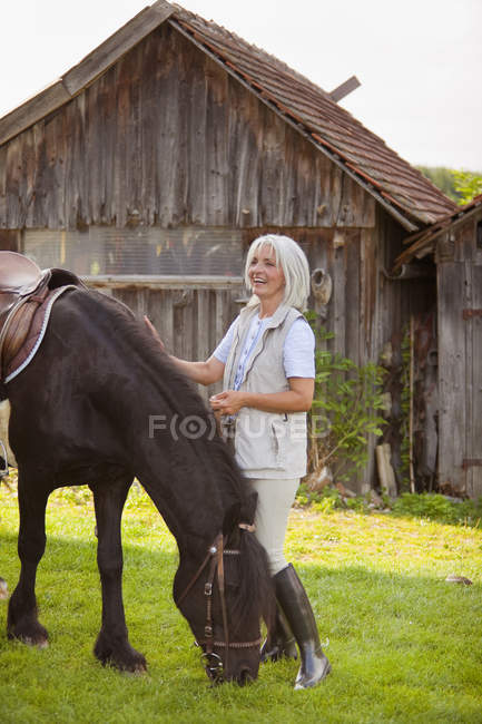 Mature woman with horse — Stock Photo