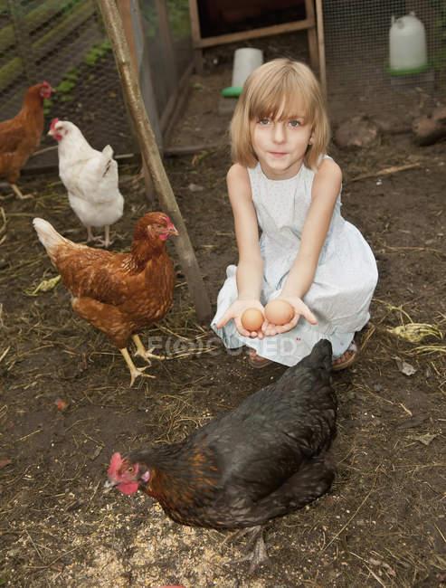 Chica con huevos en el gallinero - foto de stock