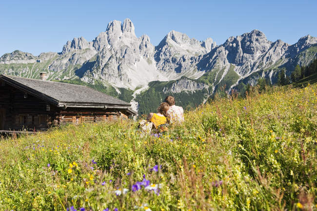Австрия, Зальцбург, Фильцмоса, пара сидеть и отдыхать в альпийском лугу — стоковое фото