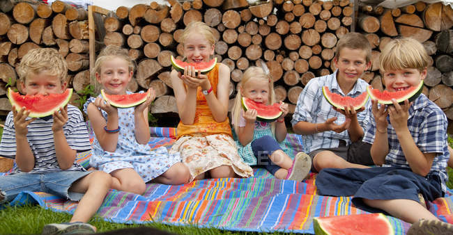 Група дітей їсть кавун в природі — стокове фото