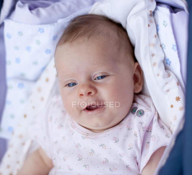 Маленькая девочка в кроватке, улыбаясь — стоковое фото
