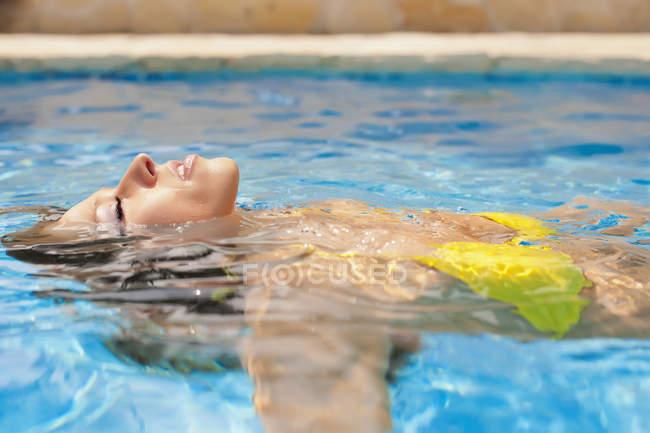 Junge Frau genießen Bad im Swimmingpool — Stockfoto