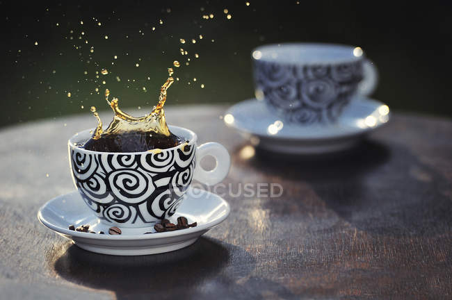Coffee splashing out of cup, coffee beans in saucer — Stock Photo