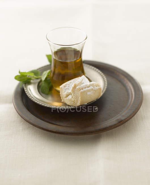 Thé noir à la menthe fraîche et de la pâte sur la plaque — Photo de stock