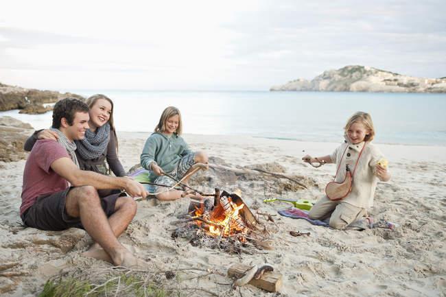 Іспанія, Майорка, друзів на грилі сосиски в табір вогонь на пляжі — стокове фото