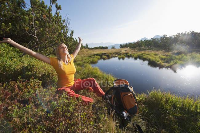 Randonneur assis près du lac de montagne — Photo de stock