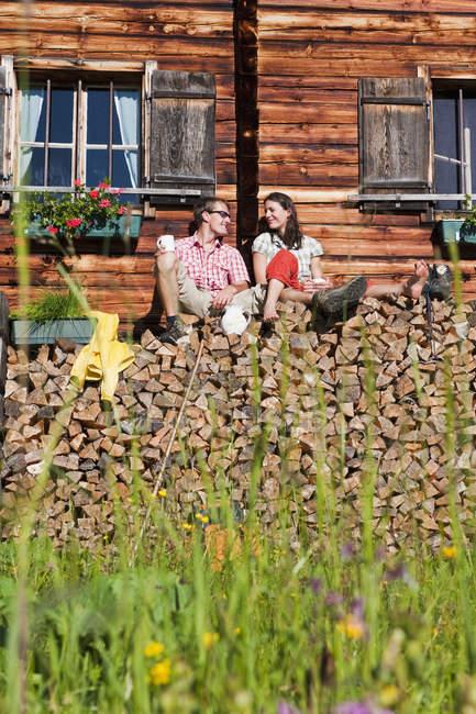 Austria, Salzburg, Couple sitting on logs by hut — Stock Photo