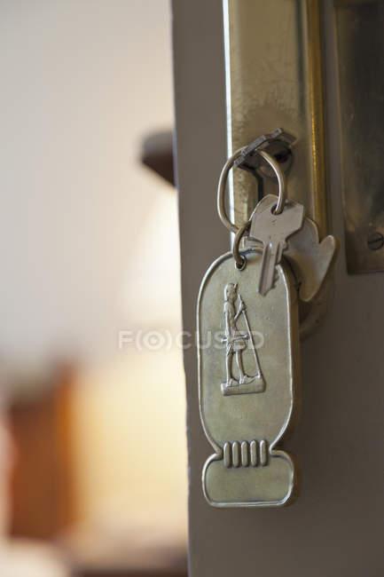 Крупный план ключа в двери отеля с брелоком — стоковое фото
