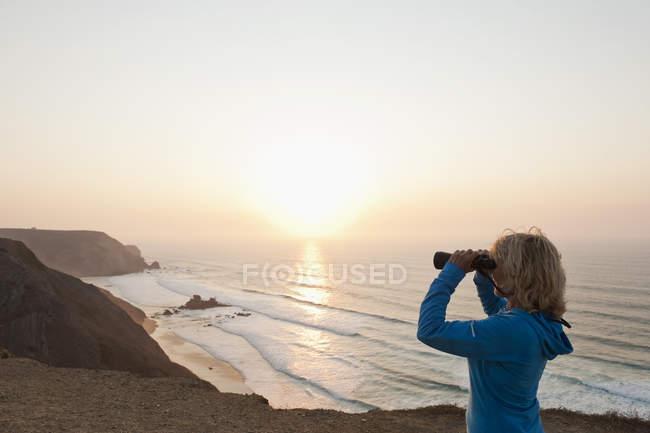 Жінка Sagres, старший Португалії, Алгарве, дивлячись на пляж через Бінокулярний — стокове фото
