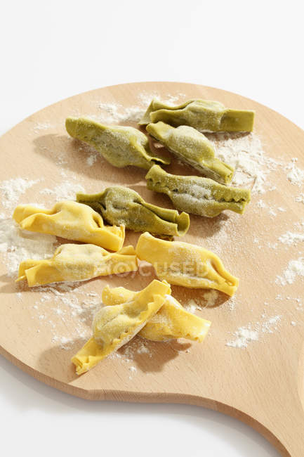 Candy shape pasta with flour on chopping board — Stock Photo