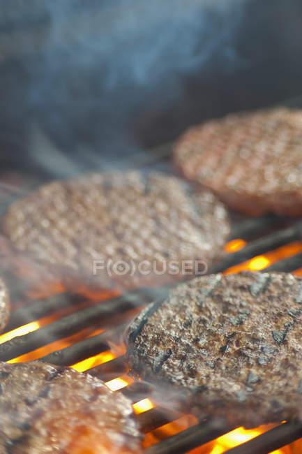 Burger Bratlinge auf Grill Rost mit Feuer und Rauch — Stockfoto