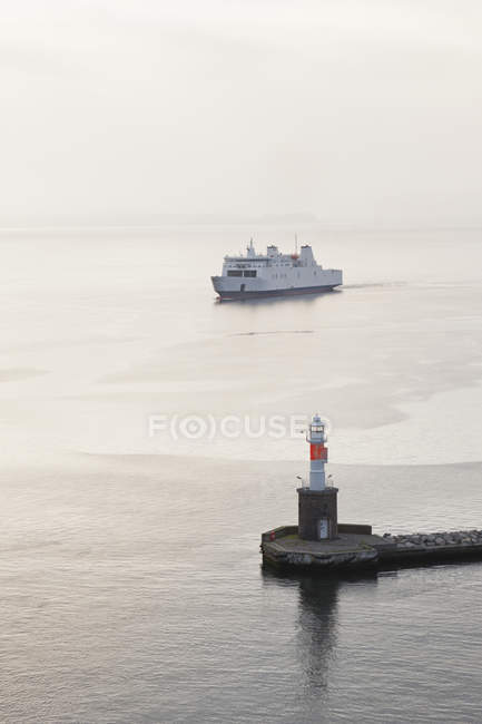 View of arriving ferryboat at harbour entrance with lighthouse at dusk, Aarhus, Denmark — Stock Photo