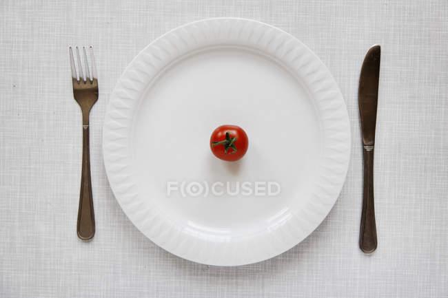 Vista superior de um tomate maduro na placa com garfo e faca na mesa — Fotografia de Stock