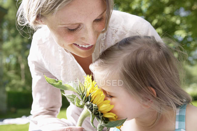 Girl smelling flower with mother — Stock Photo