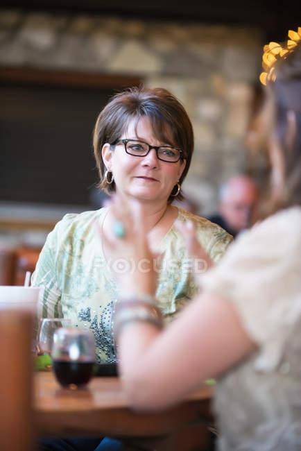 Зрілі жінки, сидіти і говорити на стіл в кафе — стокове фото