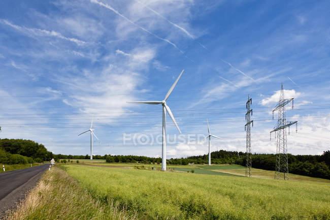 Wind turbine and electricity pylon — Stock Photo