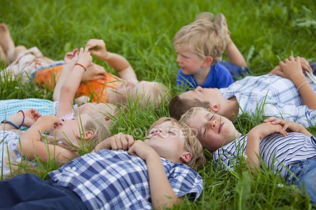 Группа детей, лежащих на лугу — стоковое фото