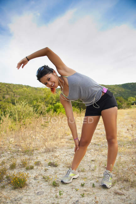 Teenage girl exercising with listening music and smiling — Stock Photo
