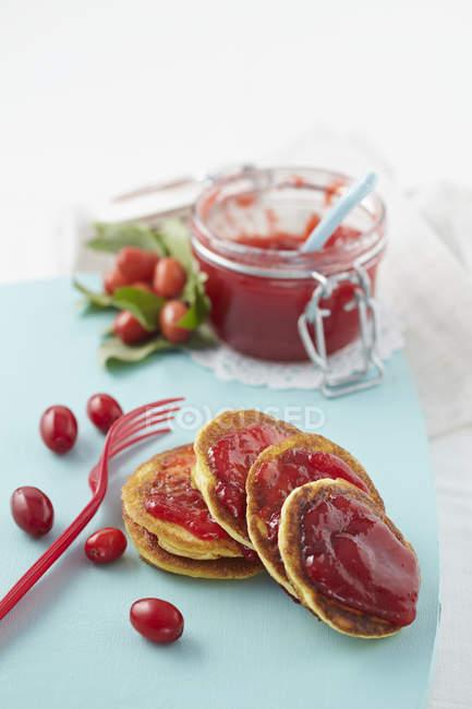 Cornel cherry jam with pancakes on chopping board — Stock Photo