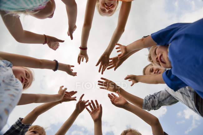 Group of children raising hands in air — Stock Photo