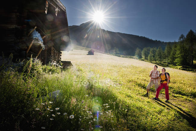 Austria, Salzburg, Filzmoos, Couple looking at alpine hut — Stock Photo