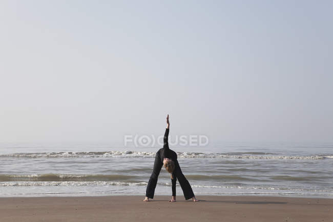 Belgium, Young woman exercising at North Sea — Stock Photo