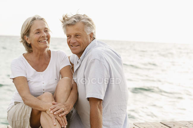 Coppia anziana seduta al mare, sorridente — Foto stock