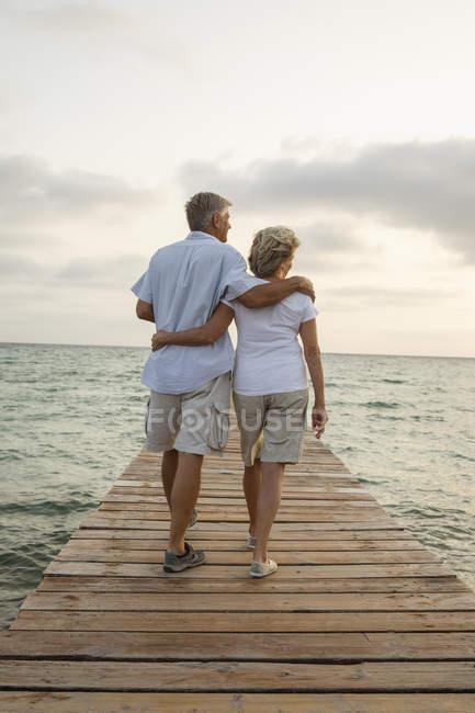 Coppia anziana in piedi sul molo al mare — Foto stock