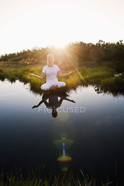 Австрия, фюльке, молодая женщина, сидящая у горного озера и занимающаяся посредничеством — стоковое фото