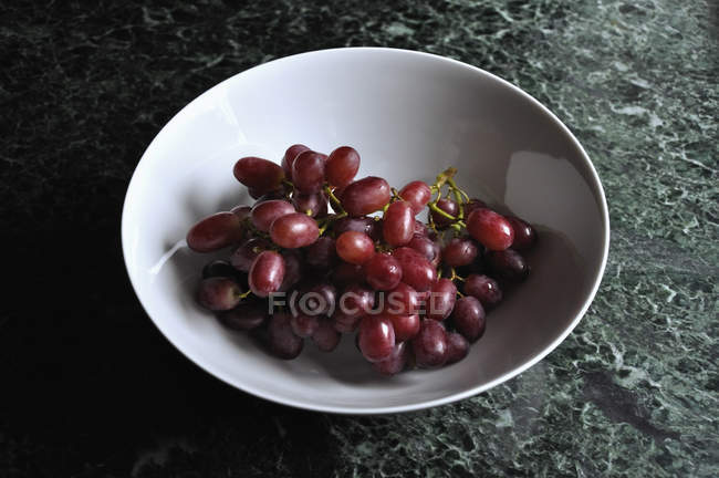 Red grapes in porcelain bowl — Stock Photo
