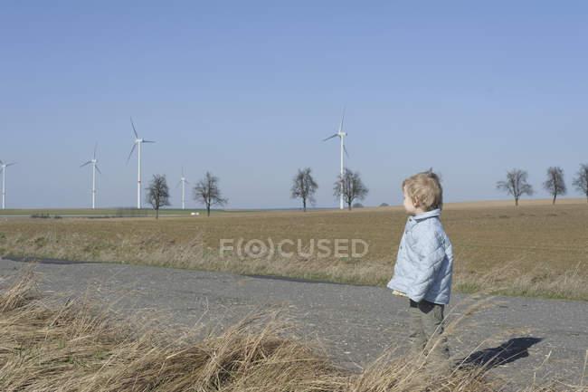Menino em pé na estrada, turbina eólica no fundo — Fotografia de Stock