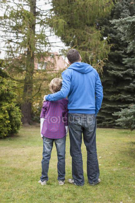 Отец и сын, стоя в саду — стоковое фото