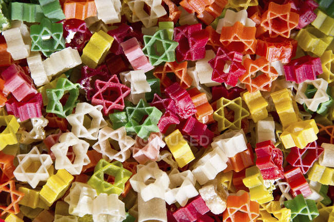 Top view of Stars of david shaped colored pasta in market — Stock Photo