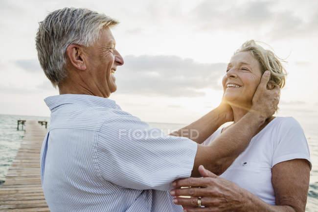 Coppia anziana che abbraccia il mare — Foto stock