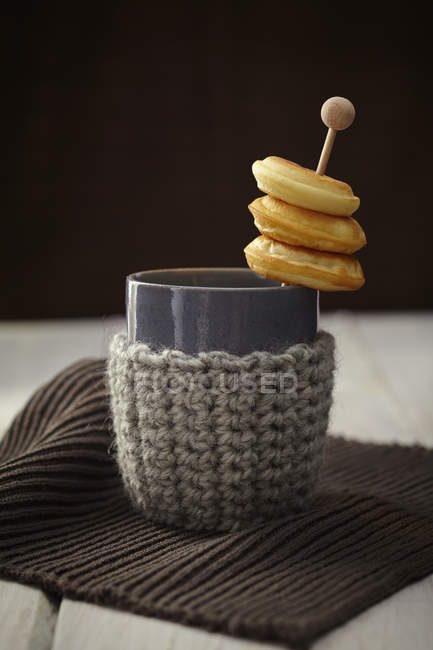 Baked doughnuts with cup and warmer on table — Stock Photo