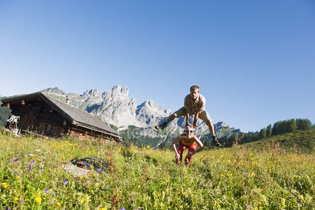 Austria, Salzburg, Filzmoos, Couple having fun in alpine meadow — Stock Photo